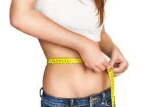 Frau misst Fett am Bauch