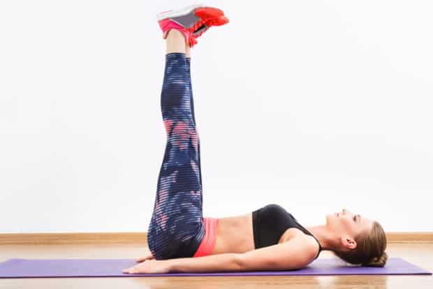 Frau liegt auf Trainingsmatte und streckt die beine nach obend