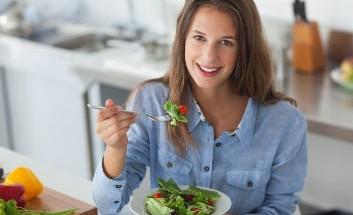 Eine Frau in der Küche beim Essen eines Salats