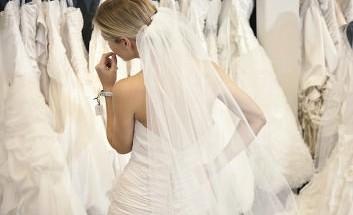 Frau in Brautkleid vor einer Kleiderstange mit vielen weiteren Brautkleidern