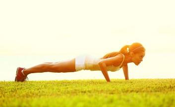 Frau in Sportkleidung führt die Fitnessübung Burpees unter freiem Himmel auf einer Wiese aus