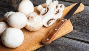 Weiße Champignons auf Holzbrett neben einem Messer mit Holzgriff