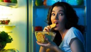 Frau nascht heimlich am Kühlschrank