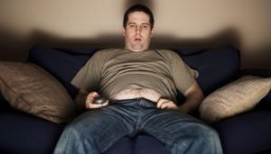 Couchpotato sitzt auf der Couch und schaut mit leerem Blick fern