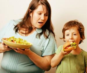 Mutter mut Salatteller in der Hand neben ihrem Sohn, der einen Burger isst