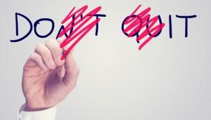 Männerhand, die aus dem an eine Glasscheibe geschriebenen Schriftzug 'Don't Quit' die Worte 'Do it' herausstreicht