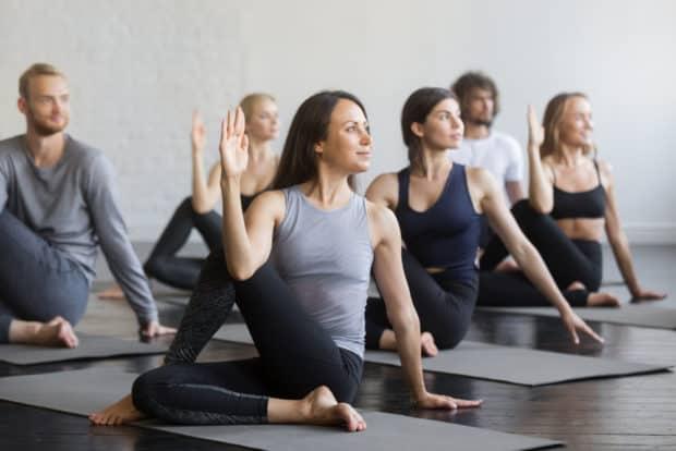 Gruppe von Frauen und Männern macht Yoga für Sportler - der Drehsitz