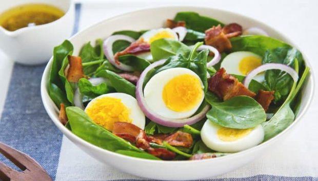 Eierscheiben mit jungem Spinat und Baconscheiben in weißer Keramikschüssel