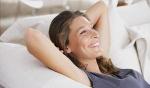 Junge Frau liegt entspannt auf dem Sofa.