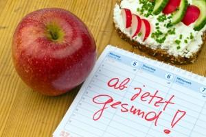 Apfel und mit Frischkäse bestrichenes Brot, daneben ein Zettel, auf dem 'ab jetzt gesund!' steht