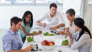 Fünf Büroarbeiter essen gemeinsam gesundes Essen zum Mittag