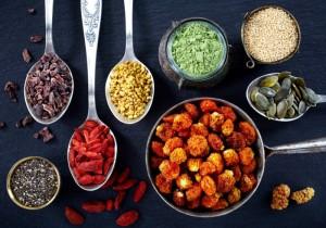 Gojibeeren, Chiasamen und andere Superfoods auf Löffeln und in Schalen präsentiert