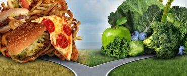 Mann im Anzug steht an einer Weggabelung zwischen Fastfood und grünem Gemüse