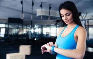 Frau im blauen Shirt schaut auf ihr Fitness Armband