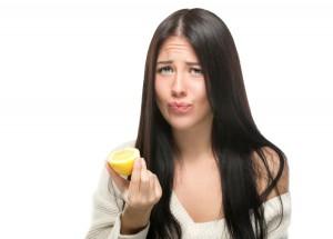 Frau verzieht nach Biss in eine Zitrone das Gesicht