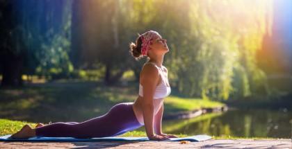 Frau führt unter freiem Himmel die Yogaübung Cobra aus