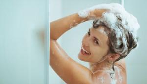Frau duscht und shampooniert sich ihre Haare ein