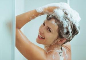 Duschende Frau beim Einshampoonieren ihrer Haare