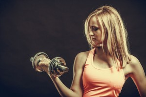 junge blonde Frau mit Hantel trainiert ihre Armmuskeln