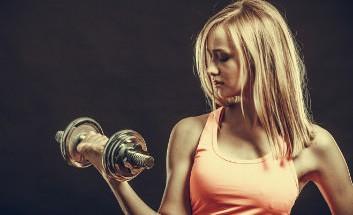Frau trainiert Bizeps Muskeln mit Hantel