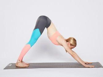 Frau bei der Ausführung der Yoga-Übung Herabschauender Hund