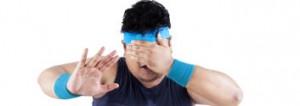 Dicklicher Mann im Sportdress, der ungesunden Verführungen mit vor den Augen gehaltener Hand widerstehen will
