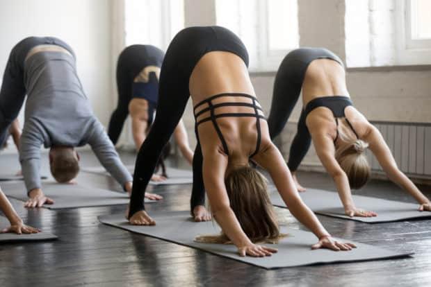 Gruppe von Männern und Frauen macht Yoga für Sportler - der herabschauende Hund