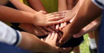 Hände die auf einem Huddle zusammen gelegt sind.
