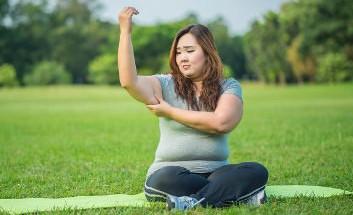 Rundliche asiatische Frau auf einer Trainingsmatte im Park, die an ihrem Winkfett zieht und dabei traurig draufschaut