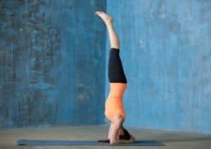 Frau schult ihre Koordination mit einem Handstand