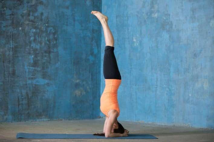 Frau schult ihre Koordination mit einem Handstand - koordinationstraining