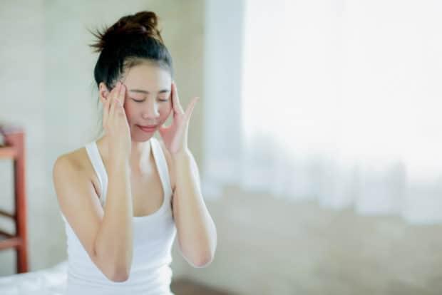 Junge Frau legt die Finger an die Schläfen, hat Kopfschmerzen