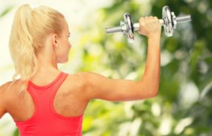 Kurzhantel Übung für den Rücken: Frau im Grünen