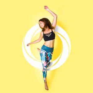 Junge Frau in bunter Leggins und Sport Top ist glücklich und macht Fitness vor gelbem Hintergrund