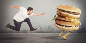 Hungriger Mann rennt einem doppelten Cheeseburger hinterher