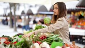 Frau kauft Gemüse auf dem Markt