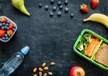 Eine vorbereitete Meal Prep Mahlzeit mit Brot, Gemüse, Obst und Mandeln