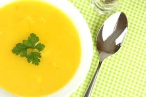 Möhren-Aprikosen-Suppe mit Petersilie in weißer Keramikschüssel