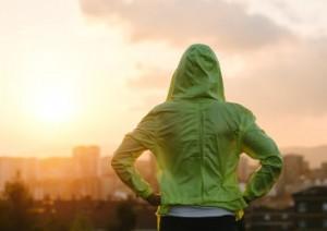 Frau im Sportdress blickt gen Sonnenuntergang