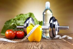 Hantel umringt von Tomate, Paprika, Salat und Wasserflasche