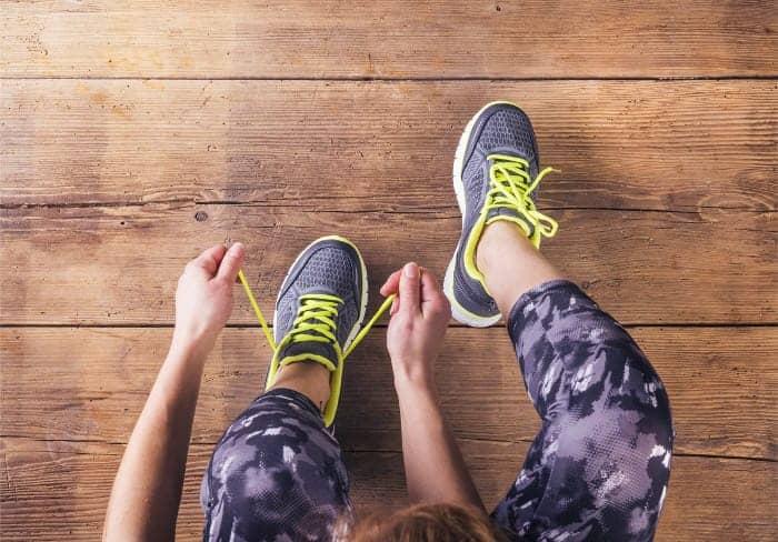 Sportlerin mit Muskelkater schnürt sich die Schuhe