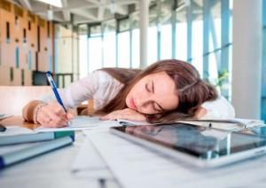 Frau schläft auf Schreibtisch