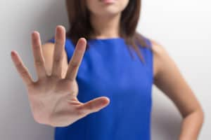 Frau in blauem Kleid streckt die Hand nach vorne und sagt Nein