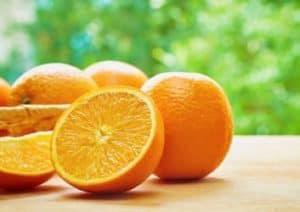 Orangen auf dem Tisch vor einem Baum.