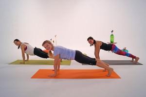 3 Frauen bei der Ausführung der Fitnessübung Planks mit gestrecktem Bein