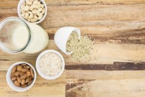 Holztisch mit Schalen voller pflanzlicher Lebensmitteln