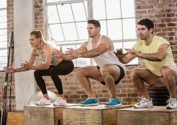 3 Sportler machen Jumping Squats