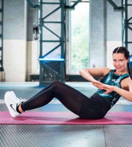 Junge Frau macht Russian Twists auf roter Trainingsmatte