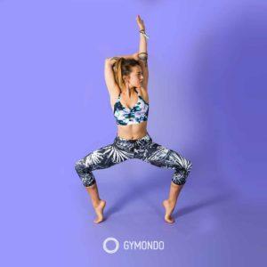 Junge Frau in bunter Leggins und Sport Top macht Fitness vor lila Hintergrund