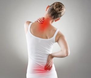 Frau fasst sich an die schmerzenden Stellen im Rücken, die rot hervorgehoben sind